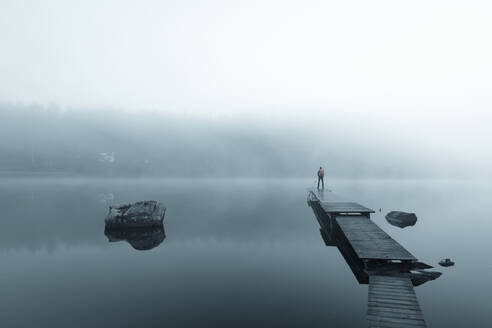 Man on pier in lake in morning fog - JOHF05024