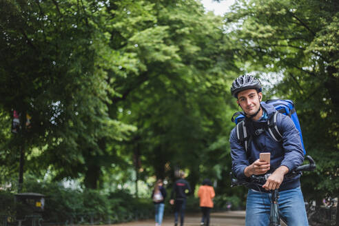Portrait of confident delivery man with bicycle against trees in city - MASF15279