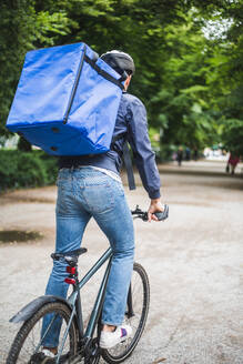 Rear view of food delivery man riding bicycle on street in city - MASF15282