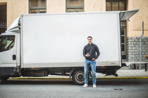 Portrait of male mover standing against truck on street in city - MASF15309