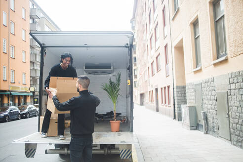 Male and female movers unloading box from truck on street in city - MASF15318