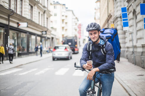 Portrait of confident food delivery man with bicycle on street in city - MASF15327