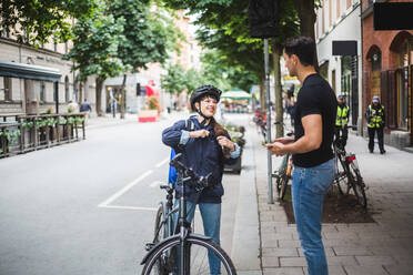 Delivery woman talking with male customer standing on sidewalk in city - MASF15342