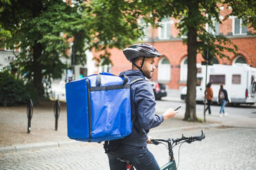 Food delivery man with bicycle looking away while standing on street in city - MASF15351