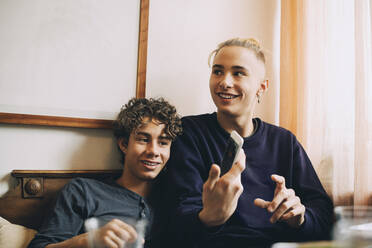 Smiling teenage boy with friend showing smart phone while looking away at home - MASF15447