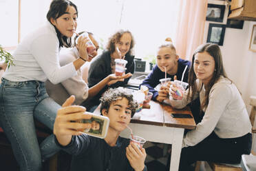 Teenage boy taking selfie with friends through mobile phone while enjoying smoothie at home - MASF15468