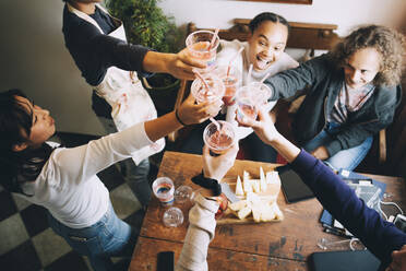 High angle view of multi-ethnic friends toasting smoothies over table at home - MASF15471