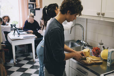 Teenage boy with female cutting fruits at kitchen counter while friends sitting in background - MASF15474