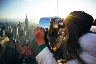 Woman on Top on the Rock looking through binoculars, New York City, United States - OCMF00948