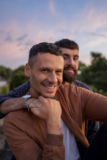 Portrait of happy gay couple outdoors at sunset - AFVF04422
