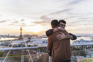 Gay couple hugging on lookout above the city with view to the port, Barcelona, Spain - AFVF04434