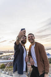 Gay couple taking a selfie on lookout above the city with view to the port, Barcelona, Spain - AFVF04437