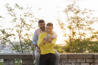 Gay couple using cell phone outdoors at sunset - AFVF04443