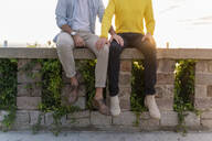 Close-up of affectionate gay couple sitting on a wall - AFVF04446