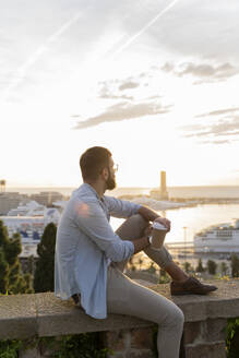 Man sitting on a wall on lookout above the city with view to the port, Barcelona, Spain - AFVF04452