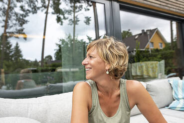 Happy woman relaxing on terrace at home - BFRF02137