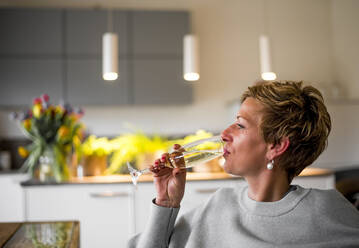 Woman drinking glass of champagne in kitchen at home - BFRF02143