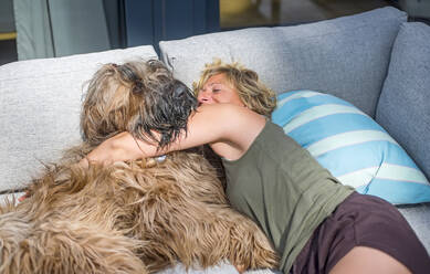 Woman cuddling with dog on terrace at home - BFRF02158