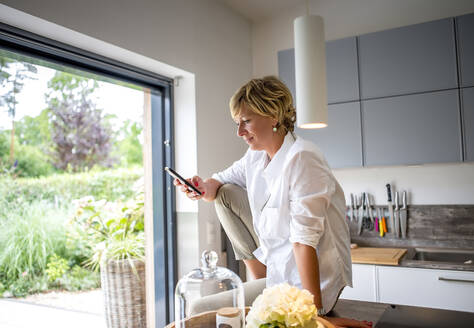 Woman using smartphone in kitchen at home - BFRF02161