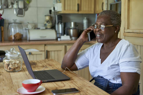 Senior woman sitting at kitchen table using laptop and smartphone - VEGF01080