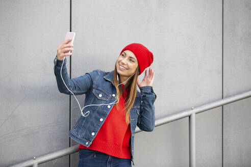 Woman wearing red pullover and wolly hat and taking a selfie - HMEF00694