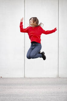 Woman wearing red pullover and dancing in front of a wall - HMEF00697