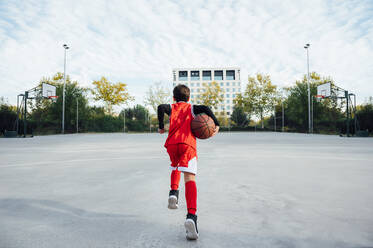 Boy playing basketball on outdoor court - JCMF00339