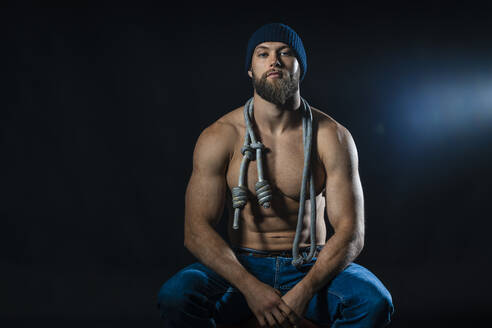 Portrait of a barechested athlete with skipping rope sitting in studio - DLTSF00314