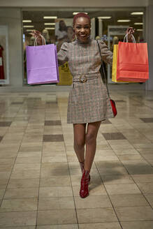 Happy young woman holding colorful shopping bags walking outside a shop - VEGF01107