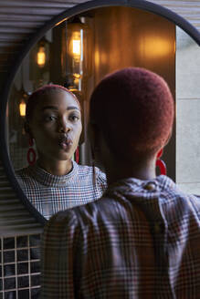 Young woman with short haircut looking to her reflection and sending a kiss in a round mirror - VEGF01134