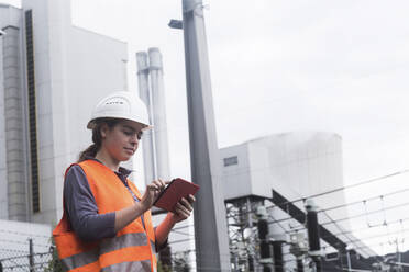 Female worker using tablet at power plant - SGF02497