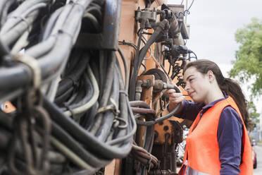 Female technician examining truck - SGF02500