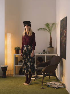 Full length of woman using virtual reality simulator while standing against wall at home - CAVF70750