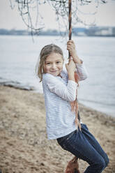 Portrait of smiling little girl swinging with rope at riverside - RORF01970