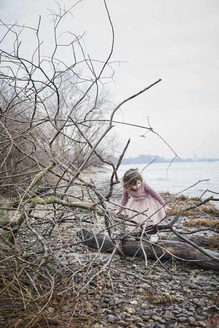 Little girl wearing pink fancy dress costume balancing on deadwood at riverside - RORF01973 - Roger Richter/Westend61