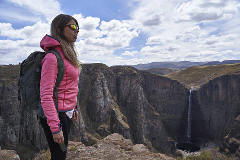 Woman standing on top of a hill at Maletsunyane Falls enjoying the view, Lesotho - VEGF01168