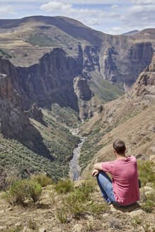 Man sitting on top of a hill at Maletsunyane Falls enjoying the view, Lesotho - VEGF01171
