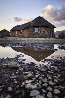 Traditional stone houses and reflection in a puddle, Lesotho - VEGF01177