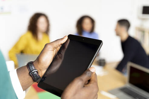 Close-up of businessman in office using tablet with colleagues in background - FMOF00828