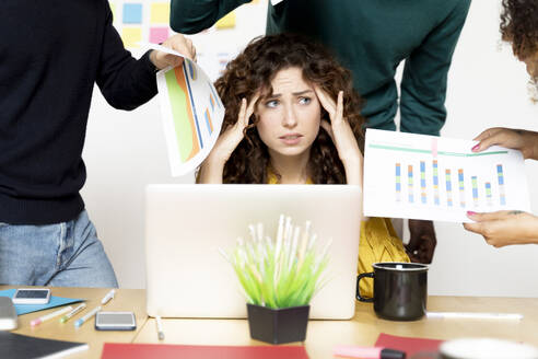 Stressed woman siting at desk in office surrounded by colleagues - FMOF00831