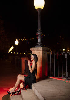 Young woman wearing black evening dress sitting on stairs at night smoking cigarette - LJF01141