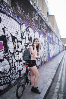 Smiling young woman on the phone at graffiti wall - FBAF01090