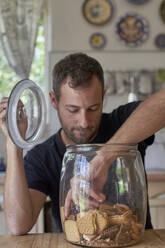 Man sitting in kitchen, looking in cookie jar, taking cokkie - VEGF01210