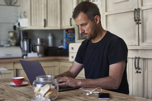Man working from home, sitting at kitchen table, using laptop and smartphone - VEGF01219