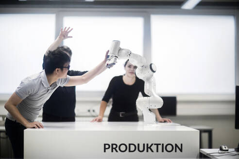 Sudents studying robotic at an university institute, discussing with professor - SGF02503