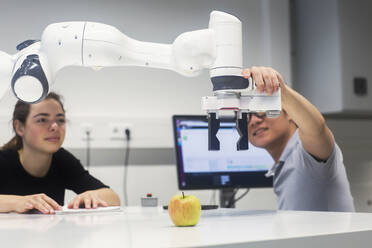 Sudents studying robotic at an university institute, making experiments with an apple - SGF02518