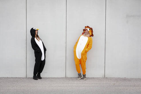 Two women in penguin and lion costume in front of concrete wall - HMEF00705