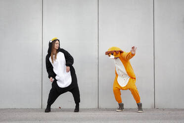 Two women in penguin and lion costume in front of concrete wall - HMEF00708