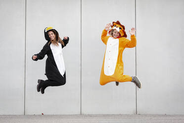 Two women in penguin and lion costume jumping in front of concrete wall - HMEF00711