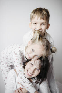 Mother having fun time with two kids on bed - EYAF00769